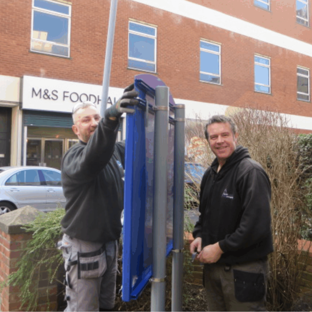 friendly people installing a notice board
